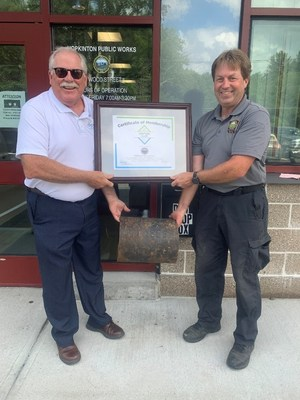 Paul Hanson, left, P.E., regional engineer for the Ductile Iron Pipe Research Association, presents Eric Carty, water and sewer superintendent for the Hopkinton, MA, Department of Public Works, with a plaque welcoming Hopkinton into the association's Century Club due to a cast-iron pipe in its water system laid in 1877 that remains in use today.